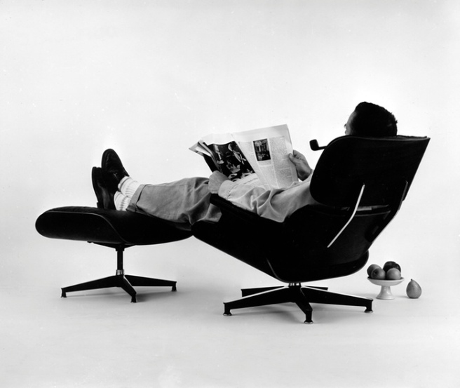 Charles Eames in the plywood Lounge and Ottoman, 1956 Photograph Eames Office