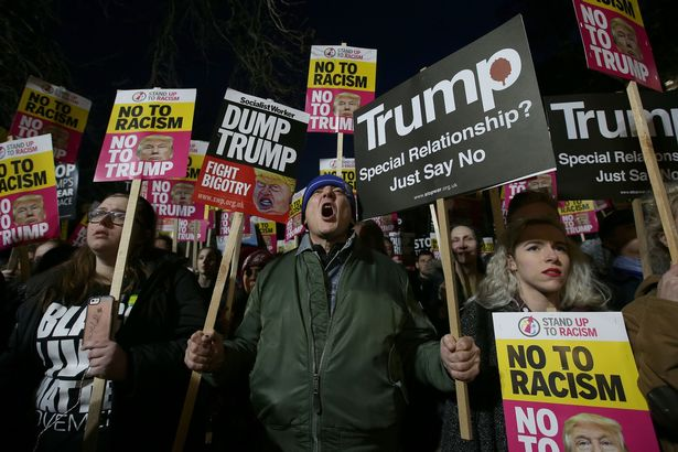 topshot-demonstrators-hold-placards-as